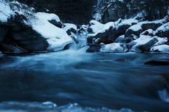 Ο χειμερινός ποταμός, το τοπίο που συλλαμβάνεται από μια θολωμένη μετακίνηση και που πλαισιώνεται από τον μπλε πάγο Στοκ εικόνες με δικαίωμα ελεύθερης χρήσης