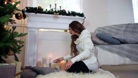 Ο χειμώνας, κορίτσι ανάβει μια συνεδρίαση κεριών από την εστία κοντά στο χριστουγεννιάτικο δέντρο, όμορφη νέα γυναίκα θερμό στον  απόθεμα βίντεο