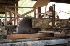 Ο χειριστής πριονιών ταΐζει το ξύλο μέσω του πριονιστηρίου ατμού Στοκ Φωτογραφία