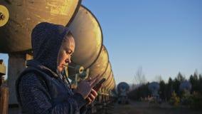 Ο χειριστής σπουδαστών γυναικών του ιδρύματος ηλιακής επίγειας φυσικής ελέγχει τον εξοπλισμό επικοινωνίας σε κινητό μοναδικός φιλμ μικρού μήκους