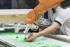 Ο χειριστής τεχνικών ρυθμίζει το αυτόματο ρομπότ Στοκ εικόνες με δικαίωμα ελεύθερης χρήσης