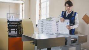 Ο χειριστής τυπωμένων υλών εξετάζει το ολοκληρωμένο προϊόν Στοκ Φωτογραφία