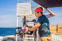 Ο χειριστής Steadicam προετοιμάζει τη κάμερα και τον σταθεροποιητής-αναρτήρα 3 άξονα για έναν εμπορικό βλαστό στοκ εικόνες