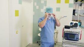 Ο χειρούργος βάζει στην αποστειρωμένη μάσκα και τα ενισχύοντας διοφθαλμικά γυαλιά πριν από τη χειρουργική επέμβαση στο λειτουργού απόθεμα βίντεο