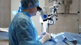 Ο χειρούργος κάνει μια περίπλοκη λειτουργία χρησιμοποιώντας ένα μικροσκόπιο φιλμ μικρού μήκους