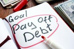 Ο χειρόγραφος στόχος πληρώνει μακριά το χρέος σε μια σελίδα στοκ εικόνα
