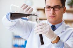 Ο χημικός μηχανικός που εργάζεται στα δείγματα πετρελαίου στο εργαστήριο Στοκ Εικόνα