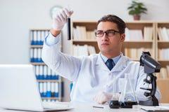 Ο χημικός μηχανικός που εργάζεται στα δείγματα πετρελαίου στο εργαστήριο Στοκ Φωτογραφία