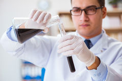 Ο χημικός μηχανικός που εργάζεται στα δείγματα πετρελαίου στο εργαστήριο Στοκ Εικόνες