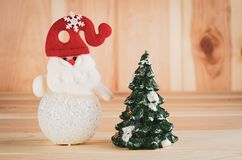 Ο χιονάνθρωπος παιχνιδιών σε ένα κόκκινο καπέλο είναι φωτεινός πυροβολισμός μεγάλος σε ένα ξύλινο υπόβαθρο στοκ φωτογραφία με δικαίωμα ελεύθερης χρήσης