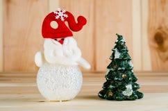 Ο χιονάνθρωπος παιχνιδιών σε ένα κόκκινο καπέλο είναι φωτεινός πυροβολισμός μεγάλος σε ένα ξύλινο υπόβαθρο στοκ φωτογραφία