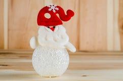 Ο χιονάνθρωπος παιχνιδιών σε ένα κόκκινο καπέλο είναι φωτεινός πυροβολισμός μεγάλος σε ένα ξύλινο υπόβαθρο στοκ εικόνες