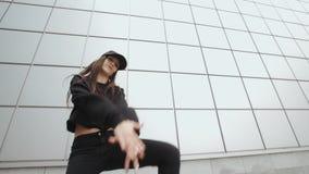 Ο χορευτής γυναικών εκτελεί το σύγχρονο χορό χιπ-χοπ, σύγχρονη ελεύθερη κολύμβηση στην οδό, αστικό περιβάλλον φιλμ μικρού μήκους