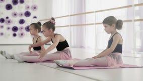 Ο χορευτής κοριτσιών θερμαίνει στο πάτωμα φιλμ μικρού μήκους