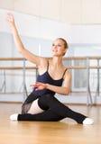 Ο χορευτής μπαλέτου κάνει τις ασκήσεις καθμένος στο ξύλινο πάτωμα Στοκ Φωτογραφία