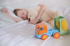 Ο 7χρονος ύπνος αγοριών με τα παιχνίδια του αντέχει και πλαστικό αυτοκίνητο Εστίαση στο αυτοκίνητο παιχνιδιών Στοκ φωτογραφίες με δικαίωμα ελεύθερης χρήσης