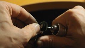 Ο χρυσοχόος αλέθει τις άκρες ενός δαχτυλιδιού με το μικρό περιστρεφόμενο αρχείο σε αργή κίνηση απόθεμα βίντεο