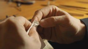 Ο χρυσοχόος κρατά το δαχτυλίδι μετάλλων με τα τσιμπιδάκια και τη θέρμανση του σε μια σόμπα κοσμημάτων σε αργή κίνηση φιλμ μικρού μήκους