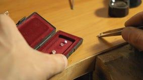 Ο χρυσοχόος παίρνει την πέτρα κοσμημάτων από το κόκκινο κιβώτιο με το pincette σε αργή κίνηση απόθεμα βίντεο