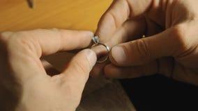 Ο χρυσοχόος παρουσιάζει τελειωμένο ασημένιο δαχτυλίδι με τον όμορφο άσπρο πολύτιμο λίθο στην κορυφή σε αργή κίνηση φιλμ μικρού μήκους