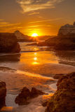 Ο χρυσός ήλιος πηγαίνει κάτω στην παραλία μεταξύ των βράχων Στοκ Φωτογραφίες