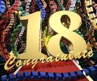 Ο χρυσός αριθμός δεκαοχτώ με τη λέξη συγχαίρει σε ένα υπόβαθρο των ζωηρόχρωμων κορδελλών και του χαιρετισμού τρισδιάστατη απεικόν απεικόνιση αποθεμάτων