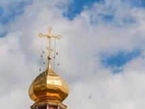 Ο χρυσός θόλος ενός ορθόδοξου ναού στο υπόβαθρο του μπλε ουρανού και των σύννεφων Χρυσός σταυρός στο θόλο του ναού Στοκ Εικόνες