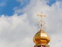 Ο χρυσός θόλος ενός ορθόδοξου ναού στο υπόβαθρο του μπλε ουρανού και των σύννεφων Χρυσός σταυρός στο θόλο του ναού Στοκ εικόνες με δικαίωμα ελεύθερης χρήσης