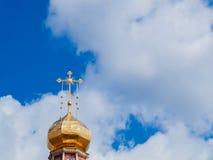 Ο χρυσός θόλος ενός ορθόδοξου ναού στο υπόβαθρο του μπλε ουρανού και των σύννεφων Χρυσός σταυρός στο θόλο του ναού Στοκ φωτογραφία με δικαίωμα ελεύθερης χρήσης