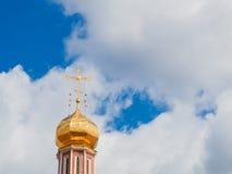Ο χρυσός θόλος ενός ορθόδοξου ναού στο υπόβαθρο του μπλε ουρανού και των σύννεφων Χρυσός σταυρός στο θόλο του ναού Στοκ Εικόνα