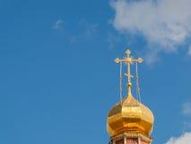 Ο χρυσός θόλος ενός ορθόδοξου ναού στο υπόβαθρο του μπλε ουρανού και των σύννεφων Χρυσός σταυρός στο θόλο του ναού Στοκ Φωτογραφίες