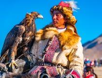 Ο χρυσός κυνηγός αετών στην πλάτη αλόγου που εξετάζει καλά - εκπαιδευμένος αετός στοκ εικόνα