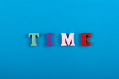 Ο χρόνος δημιουργεί Χρόνος Word που συντίθεται από τις ζωηρόχρωμες ξύλινες επιστολές στο μπλε υπόβαθρο Στοκ εικόνα με δικαίωμα ελεύθερης χρήσης