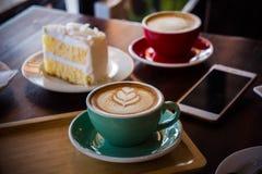 Ο χρόνος καφέ στον ξύλινο επιτραπέζιο καφέ, πίνει τον καφέ και το νόστιμο κέικ Στοκ Φωτογραφία