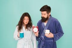 Ο χρόνος καφέ του Κάθε πρωί αρχίζει με τον καφέ Ζεύγος στα μπουρνούζια με τις κούπες Ο άνδρας με τη γενειάδα και η νυσταλέα γυναί στοκ φωτογραφία με δικαίωμα ελεύθερης χρήσης