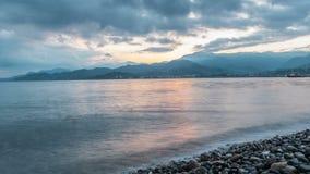 Ο χρόνος πριν από τον ήλιο αυξάνεται κοντά στον ωκεανό Τα όμορφα βουνά και τα σύννεφα είναι φωτισμένα στον πορτοκαλή ήλιο αύξησης απόθεμα βίντεο