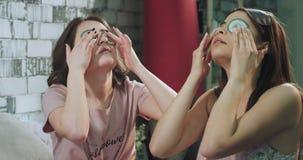 Ο χρόνος Beaty για νέες κυρίες το πρωί έχει μια ρουτίνα γιατί ένα πρόσωπο κάνει μια μάσκα ματιών από το αγγούρι στις πυτζάμες απόθεμα βίντεο
