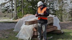 Ο χτίζοντας επιθεωρητής γράφει κοντά στα δομικά υλικά απόθεμα βίντεο