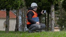Ο χτίζοντας επιθεωρητής παίρνει τις εικόνες στο PC ταμπλετών κοντά στο δέντρο απόθεμα βίντεο