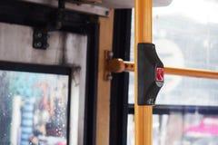 Ο χτυπώντας διακόπτης ηλεκτρικών κουδουνιών λεωφορείων ` s πρακτικός εγκαθιστά στον κίτρινο σωλήνα κιγκλιδωμάτων Στοκ Εικόνες