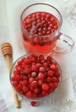 Ο χυμός και τα μούρα Ranberry σε ένα γυαλί σε ένα άσπρο τραπεζομάντιλο λινού, κλείνουν επάνω Στοκ Εικόνα