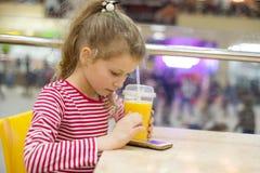 Ο χυμός κατανάλωσης παιδιών κοριτσιών στον καφέ εξετάζει το smartphone, ψωνίζοντας κέντρο ψυχαγωγίας λεωφόρων υποβάθρου Στοκ εικόνα με δικαίωμα ελεύθερης χρήσης