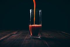 Ο χυμός ντοματών χύνεται σε ένα εδροτομημένο πολύτιμους λίθους γυαλί σε ένα μαύρο backgroun στοκ φωτογραφίες με δικαίωμα ελεύθερης χρήσης