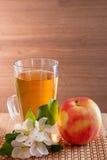 Ο χυμός της Apple σε ένα γυαλί, ένα μήλο και ένα Apple-δέντρο ανθίζει σε ένα ξύλινο υπόβαθρο Στοκ Εικόνες