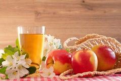 Ο χυμός της Apple σε ένα γυαλί, τρία μήλα και Apple-δέντρο ανθίζει σε ένα ξύλινο υπόβαθρο Στοκ εικόνες με δικαίωμα ελεύθερης χρήσης