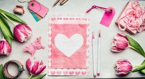 Ο χώρος εργασίας των γυναικών άνοιξης με τις ρόδινες τουλίπες ανθίζει, φάκελος εγγράφου με την καρδιά, δείκτες βουρτσών, ετικέττε Στοκ Εικόνες