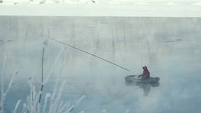 Ο ψαράς αλιεύει στον ποταμό από τη βάρκα η αλιεία του πάγου βρίσκεται ακριβώς παγιδευμένος χειμώνας zander φιλμ μικρού μήκους