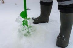 Ο ψαράς κάνει μια τρύπα στον πάγο για το βλαστό χειμερινής fishingcloseup λεπτομέρειας Στοκ εικόνες με δικαίωμα ελεύθερης χρήσης