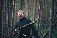 Ο ψαράς κυνηγών θέτει στη δασική ακτή ποταμών Στοκ Φωτογραφίες