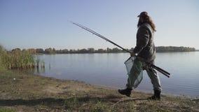 Ο ψαράς με τη μακριά γενειάδα περπατά κοντά στον ποταμό με την αλιεία των ράβδων και της στεφάνης ενέδρας καθαρών κίνηση αργή φιλμ μικρού μήκους